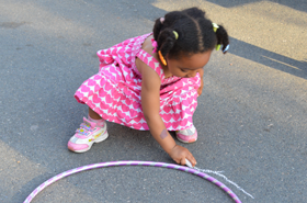 a young Somerville MA child playing with a hulu hoop